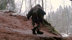 Prehistoric caveman goes outside from his cave on a background of winter forest Stock Footage