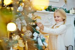 Adorable child decorating traditional xmas evergreen tree at home Stock Photos