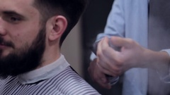 Male barber make a haircut for bearded client and using a talc at barbershop Stock Footage