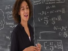 Happy black woman teaching mathematic equations on chalkboard. Stock Footage