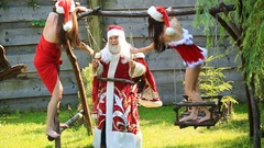 Santa Claus swinging on a wooden swing with two pretty sexy girls Stock Footage
