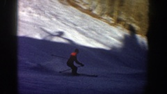 1961: a man is skiing down a mountain slope, doing a slalom from right to left Stock Footage
