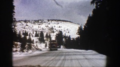 1961: driver heads toward mountain passing truck in opposite lane on snowy road Stock Footage