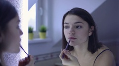Young beautiful woman applying lip gloss in bathroom Stock Footage