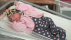 Newborn baby girl lying on medical couch. Close up Stock Footage