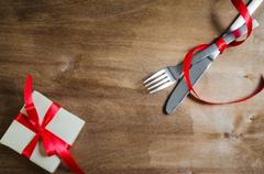 Present and Silverware Tied with Red Ribbon on Wooden Background. Stock Photos