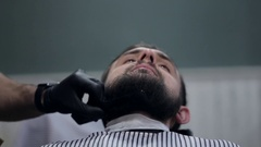 Male barber cutting beard with electric razor at a barber shop. Stock Footage