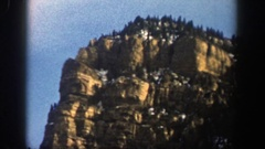 1961: boulder-covered mountain peak with forest and pockets of snow under a blue Stock Footage