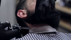 Male barber cutting beard with scissors at a barber shop. Stock Footage