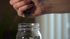 Female hand dropping a large handful of coins into a jar. Stock Footage