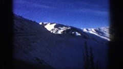 1961: car ascending snow-covered mountain range under blue sky with wispy, long Stock Footage