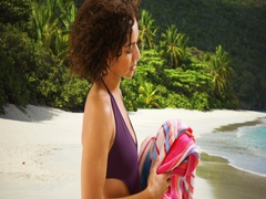 Portrait of black woman standing on tropical beach wiping face with towel. Stock Footage
