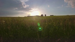 Aerial field green grass countryside landscape flatland meadow sky sunset sun Stock Footage