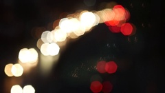 Urban traffic scene at night with bokeh lights from cars on the road Stock Footage
