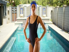 Attractive young black woman standing in front of pool in one-piece swimwear. Stock Footage