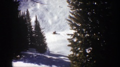 1961: small snow covered hills with young conifers adjacent and skier in the Stock Footage