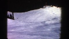 1961: four skiers are leisurely skiing downhill as seen from a stationary point Arkistovideo