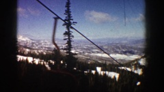 1961: riding the chair of a ski lift and viewing the surrounding valleys and Stock Footage