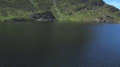 Aerial drone footage of ocean by mountain landscape Stock Footage