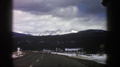 1961: driving on blacktop with snow on the sides and adjacent mountainsides Stock Footage