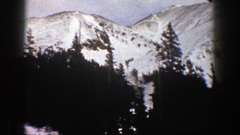 1961: panorama of a snowy mountain valley with trees and jagged peaks and a road Stock Footage