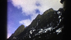 1961: snow clings to the side of a forested mountain slope on a partial cloudy Stock Footage
