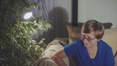 Portrait of laughting eldery woman sitting on the armchair Stock Footage