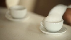 Small hands take off the table the cup with whipped cream in a café Stock Footage