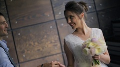 Bride and groom holding hands on photo shoot inside Stock Footage
