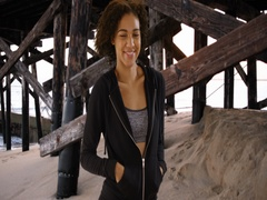 Happy black woman standing on beach by pier, smiling. Stock Footage