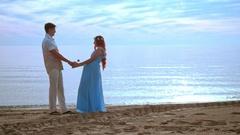 Couple holding hands on sea beach at sunrise. Pregnant couple beach Stock Footage