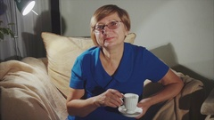 Happy senior woman drinking tea sitting on the chair Stock Footage
