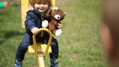 Happy kid on a swing with a brown teddy bear Stock Footage