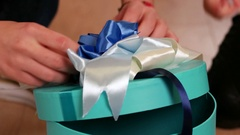 Gift wrapping, girl knits bow on a box with a gift, a holiday surprise for Stock Footage