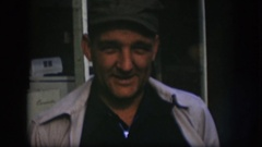 1958: middle aged man wears cap, talks, turns head, leans and lifts one side of Stock Footage