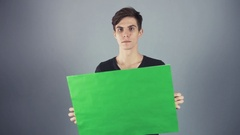 Smiling Young man in black shirt holding green key sheet poster gray background Stock Footage
