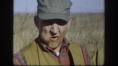 1958: two guys out hunting, standing with guns, one chewing tobacco, one with a Stock Footage