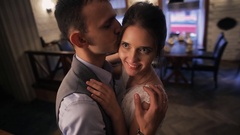 Groom at restaurant gently kisses beloved in temple Stock Footage