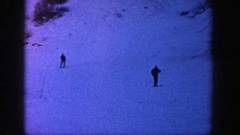 1961: two people leisurely skiing down a mountain in the evening twilight. ASPEN Stock Footage