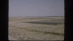 1958: road divides field which is smooth and wavy on one side and sharply angled Stock Footage