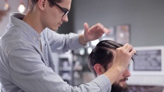 Barber combing the hair of the client before haircut at a barber shop Stock Footage