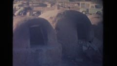 1951: primitive outdoor kilns sit in a barren field next to a busy road NEW Stock Footage