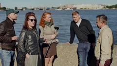 Tourist group and guide discussing on embankment on background of big river shot Stock Footage