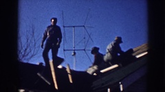 1958: three men on house roof laying shingles below antennae, bare branches and Stock Footage