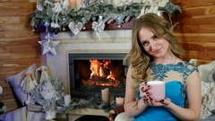 Beautiful girl drinking tea at home, Decorated Christmas tree on background Stock Footage