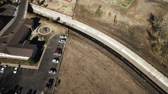 2016: an aerial view of a road leaving an undeveloped area and entering a Stock Footage