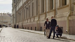 Group of men wait for something on background of old city center street, one Stock Footage