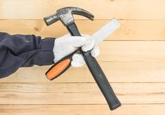 Hand in glove holding chisel and hammer Stock Photos