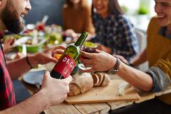 Man pouring homemade red wine to his friend by Thanksgiving table Stock Photos