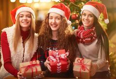 Attractive Santa girls with xmas gifts looking at camera Stock Photos